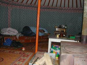 Jurtan keskellä oli joitain huonekaluja ja hevosen lannalla lämpiävä kamiina.