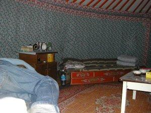 Jurtta sisältä. Seinät ovat päällystetty kankailla ja huonekalut kiertävät seiniä.