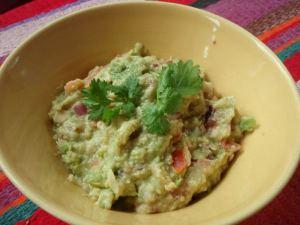 Rosoisempi guacamole, joka on tehty haarukalla ja jossa on joukossa tomaatin ja punasipulin paloja.