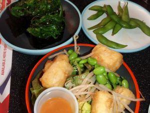 Edamamea japanilaisessa ravintolassa. Ylhäällä oikealla edamamet, alhallaa inarisushia ja salaattia, jossa on edamame-papuja ja ylhäällä vasemmalla merileväsushia.