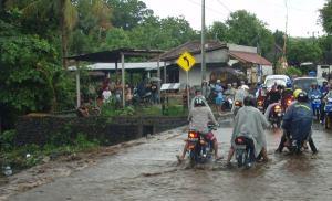 Mopot ylittävät tulvivaa jokea Balin Tulambenissa.