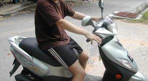 Turisti ja skootteri. Tämän mopon alle jäin, kun yritin sillä ajaa Langawilla.