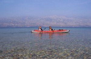 Kanootissa Razanacissa. Edessä kirkasta vettä ja takana Dalmatian kukkulat.