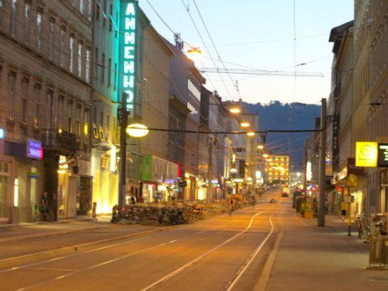Grazin Annenstrasse illalla. Tien päässä on rautatieasema ja sen takana kukkuloita.