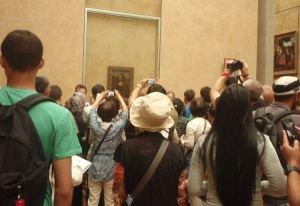 Turisteja valokuvaamasssa Mona Lisaa.