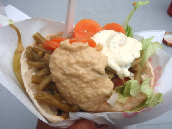 Mr Falafelin pitafalafel, jossa falafel-pyörykät ovat peittyneet vihannesten, hummuksen ja tahini-kastikkeen alle.