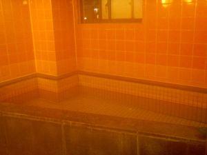 Kapselihotellin kylpyosaston höyryvä kuumavesiallas.