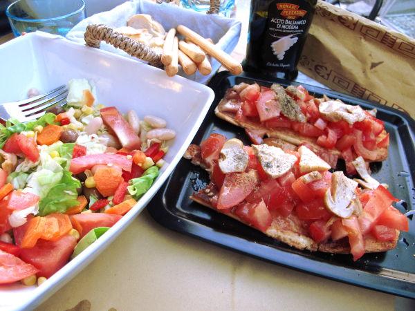 Herkkutateilla ja tomaatilla päällystettyä bruschettaa ja papusalaattia.