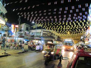 Khao San Roadin alkupäässä kulkee tämä Thanon Tanao. Liput ilmassa liittyvät joko juuri olleeseen kuninkaan syntymäpäivään tai keltapaitojen mielenosoituksiin.