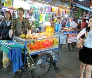 Näitä hedelmäkärryjä on Bangkokissa kaikkialla. Hedelmäpussin hinta turisteille vaikuttaa olevan vakio 20 bahtia, mutta puolikkaan ananaksen olen saanut 15 bahtillakin ja jossain paikoissa turistilta yritetään pyytää 30-40 bahtiakin. Muiden hedelmäkärryjen myyjät eivät ole näin hipstereitä kuin tämä KSR:n myyjä.