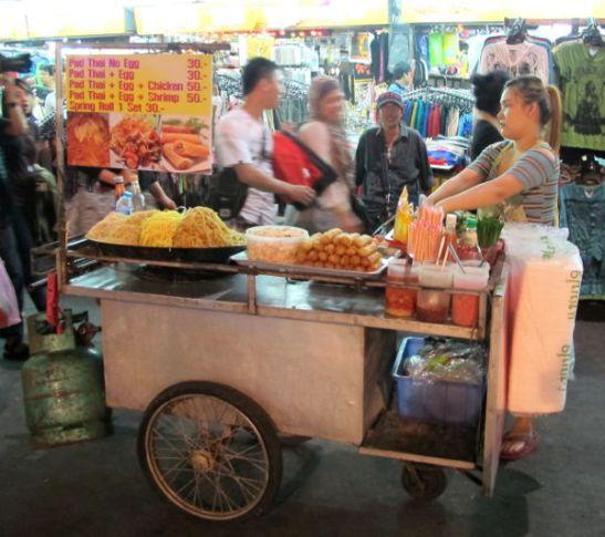 Pad thai -nuudelikärryt Khao San Roadilla. Ne pitää pyytää ilman kananmunaa. Muualla ei yleensä taida olla tällaisia pad thai -kärryjä, koska thaimaalaiset itse nauttivat nuudelinsa hieman toisenlaisina. Tämä onkin kai vain turistiversio.