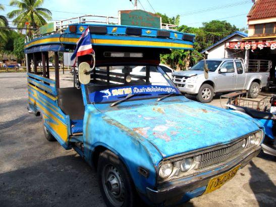 Taksin ja bussin virkaa toimittava songtau-auto.