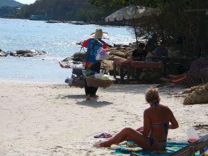 Ainakin Koh Sametilla rannalla liikkuu hedelmien myyjiä, joten hedelmäaamiaisen voi syödä biitsilläkin. Tässä kuvassa myyjän olalla on papaijasalaatin tekotarpeet, mutta samanlaisten korien kanssa liikkui myös hedelmäkauppiaita.