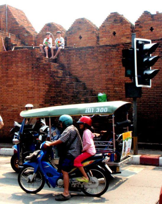 Pikkupojat ampumassa ohiajajia vanhan kaupungin muurilla. Songkranin aikaan tapahtuu moninkertaisesti liikenneonnettomuuksia muihin aikoihin verrattuna.