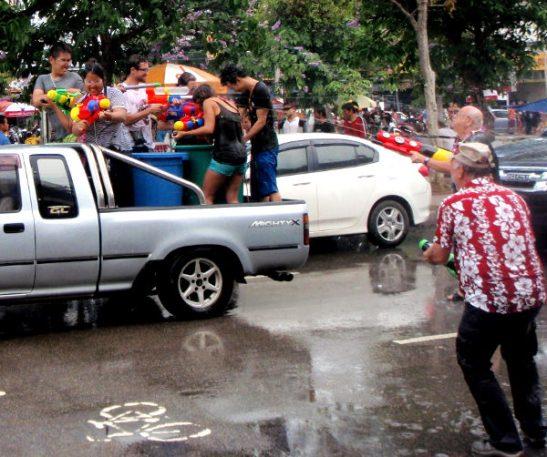 Monet viettävät songkranin auton lavalla vesipyssyllä ampuen.