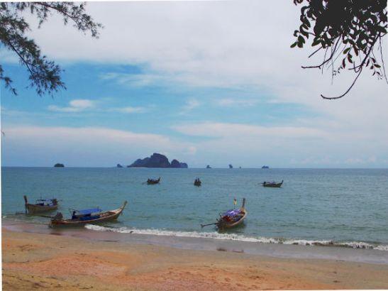 Tyypillinen näkymä Ao Nangin rannalta merelle, jossa on pitkähäntäveneitä ja äkkijyrkkiä saaria ja luotoja.