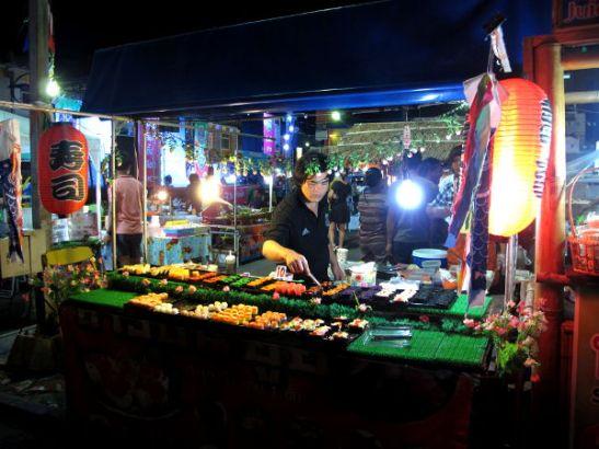 Sushikoju viikonlopputorilla. Näitä kojuja näkee yleensä aina Thaimaan iltatoreilla ja niistä löytyy yleensä vegaanisena ainakin wakame-merileväsalaatilla päällystettyjä sushirullia 5 tai 10 bahtin kappalehintaan.