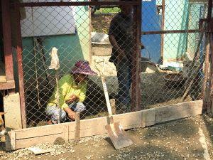 Palkatut henkilöt korjaamassa koirien ulkoilueteistä. Tuon eteisen kautta koirat saadaan vietyä portista ilman että koko tarhan koirat livahtaisivat karkuun. Silti usein tuottaa hankaluuksia saada kävelylle intoilevat koirat tieltä kantaessaan jotakuta toista koiraa ulkoilua varten ulkoilueteiseen.
