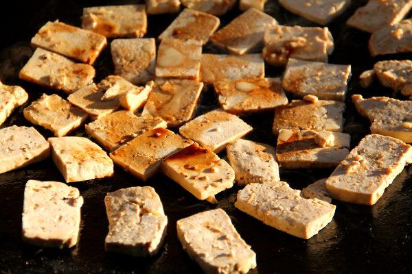 Sinappitofut paistumassa. Ohuemmat ja pienemmät viipaleet ovat Jalotofua ja paksummat ja isommat viipaleet ovat Alpron tofua. Alpron tofu murenee helpommin, joten paistaessa se on parempi viipaloida paksummaksi.