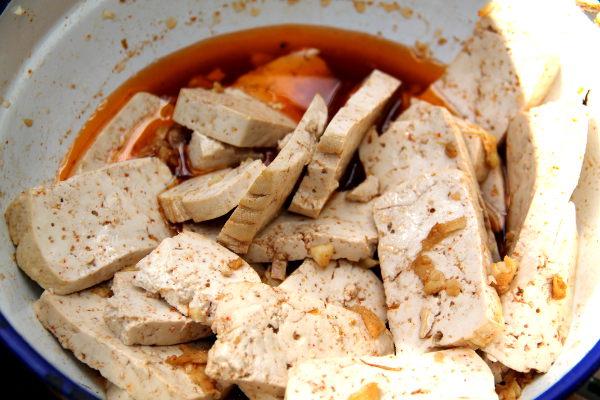 Tofut marinoitumassa valkosipulin, inkiväärin, soijakastikkeen, sitruunan ja paprikamausteen sekoituksessa. Punainen sävy tulee paprikasta.