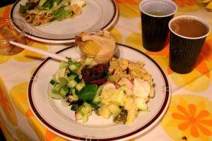 Rauhanbrunssin salaatit ja jälkiruoka (lautasella ylhäällä uuniomenat vaniljakastikkeella, hummus, perunasalaatti, tuoresalaatti ja keskellä tapenade tms. Oli myös leipiä, kahvia, teetä, mehua ja muffinsseja. Kaikki oli vegaanista.