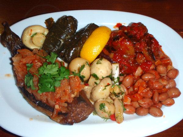 """Tällaisia kasvisruokia sain tavallisesta turkkilaisesta ravintolasta istanbulin vanhasta kaupungista. Istanbulissa näkyi ravintoloita, joissa ruokia on valmiina tiskillä vitriinin alla. Niissä on helppo osoitella mitä haluaa. Vaikutti helpolta päätellä ruoan ulkonäöstä sopivatko ne vegaanille, mutta ruokia osoitellessa on hyvä varmistaa """"is it vegetarian?"""" ja jos mietit onko jokin vegaanista, niin varmistaa vielä """"is there milk in it? Or yoghurt?"""". Tässä on täytettyä munakoisoa, viininlehtikääryleitä, marinoituja herkkusieniä, papuja ja jotain."""