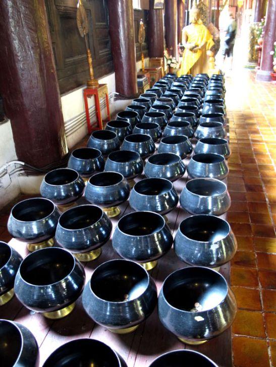 Nämä ovat käsittääkseni munkkien ruukkuja, joihin he keräävät/ovat keränneet ihmisten ruoka yms. lahjoituksia. Munkit eivät siis kerjää, vaan antavat ihmisille mahdollisuuden hyvän karman hankkimiseen.