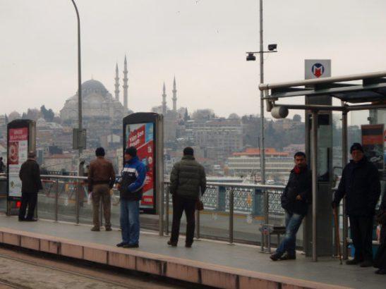 Ukkoja Galata Köprüsün sillalla Karaköyn ratikkapysäkillä. Takana Sultanahmetin kaupungiosaa ja pari moskeijaa, mm. Suleimanin moskeija.