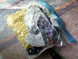 Ilmattomaksi pölynimurilla imaistu vakuumipussi, jossa on noin kymmenen isoa t-paitaa ja kolmet ohuet pitkät kangashousut.