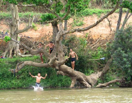 Poikia hyppimässä jokeen.
