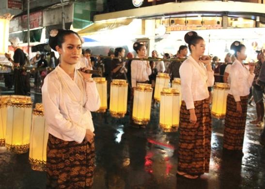 Lyhtyjen kantajat ensimmäisen päivän paraatissa samalla kadulla missä on joka iltainen Night Bazaar Chiang Maissa.