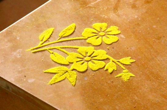Joitain koristekuvioita tehdään hiekasta sapluunaa hyväksi käyttäen, mutta perinteisimmät tehdään ympyrämuotoon käsivaralla.