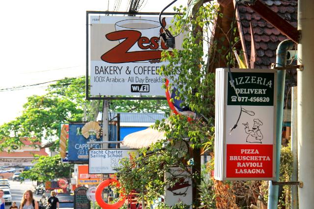 Mae Haadin ravintolakylttejä. Etualalla hyvä italialainen Famoso, sitten Zest ja sen takana Cappucino. Kuvan ulkopuolelle jäi ylempänä mäkisellä kadulla oleva kasvisravintola.