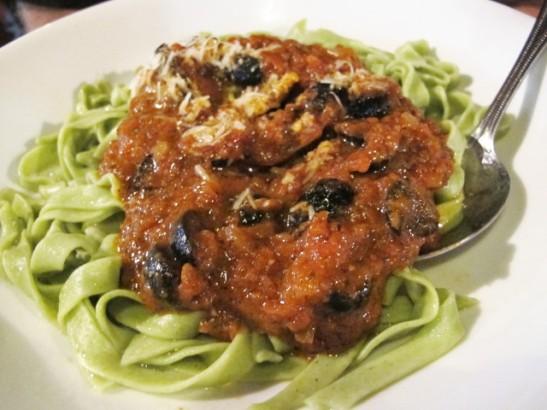 Famoson oliivi-tomaattipasta vihreällä fettucinella. Annokset pitää muistaa pyytää ilman juustoa ja sanoa ehkä vielä erikseen että ei parmesaania, koska kokki laittaa sitä automaattisesti.