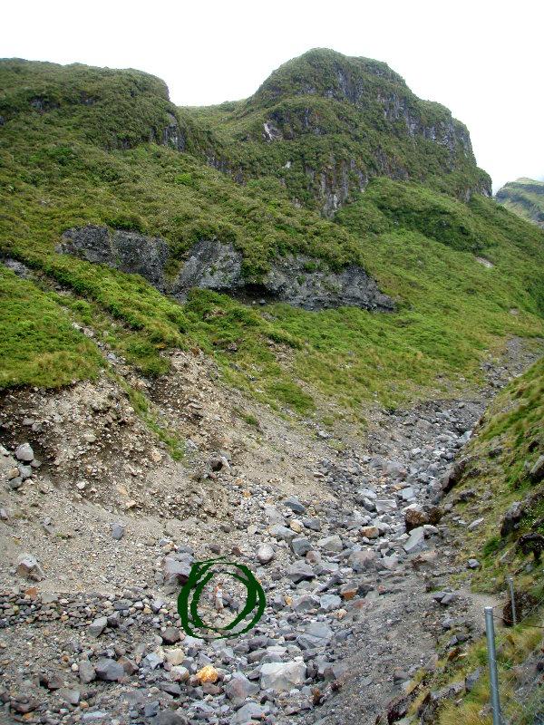 Vuoren rinnettä, ympyröitynä näkyy pienenä ihminen.