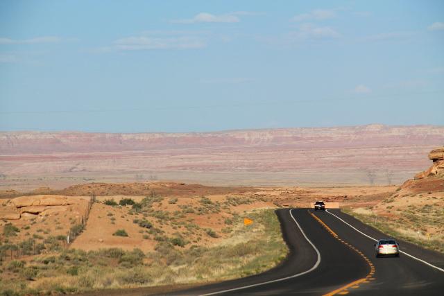 Painted desert tässä taustalla on pitkä kallioalue, jossa kallio näyttää kuin monilla väreillä maalatulta.