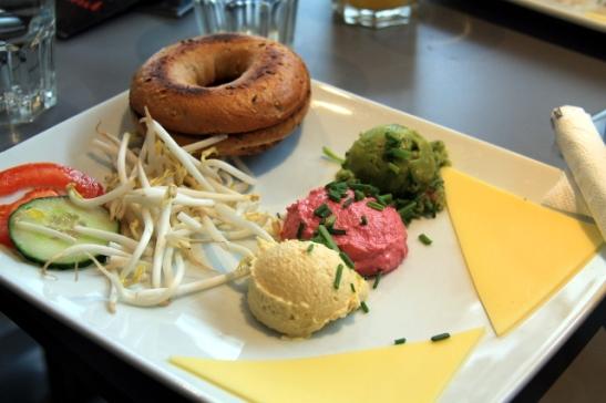 """""""Vegan Power"""" -bagelannos, jossa kokkäreet tavallista hummusta, punajuurihummusta ja avokadotahnaa. Lisäksi pari viipaletta vegaanijuustoa (8,90 euroa sis. appelsiinimehun ja kahvin)."""