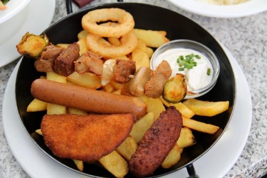 Schillingerin majatalon vegaani lihaisa gusto pan, jossa on ranskalaisten päällä pari sipulirengasta, varras, makkara, täytetty feikkilihaköntti ja joku mausteinen köntti. Näitä sai dipata majoneesiin.