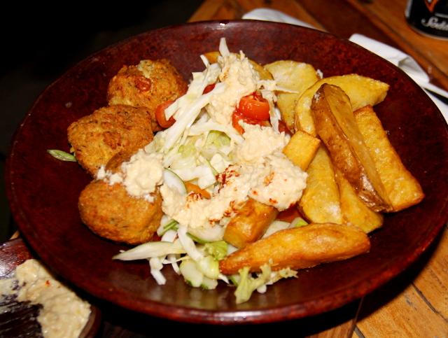 Ikanin falafellautanen, johon tuuppaistu hummukset falafelien, ranskisten ja salaatin päälle.