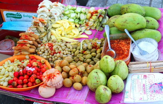 Erikoisen näköistä ruokaa Phnom Penhin kadulla. Kyse taitaa olla happaman makuisista raaoista mangoista ja pikkelöidyistä vihanneksista, jotka syödään chilitahnan kera. Tuollaisissa chilitahnoissa on useimmiten katkarapua ja kalakastiketta.