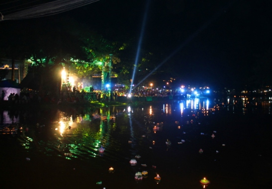 Vesifestivaalien valoja ja kelluvia kratongeja joessa.