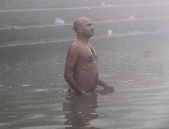 Mies kylpemässä Gangesissa.