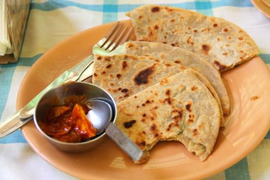 Seva´sin paranthaa ja acharia. Paranthalätyt paistetaan usein voissa, joten vegaanin on niitä usein vaikea tilata. Näiden paranthojen sisällä oli raastettua perunaa, joka näytti juustoraasteelle. Achar tarkoittaa tuollaista suolaista pikkelöityä lisäkettä, jossa on usein käytetty raakaa mangoa.